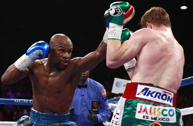 Floyd Mayweather Jr. throws a punch at WBC/WBA 154-pound champion Canelo Alvarez during their title fight at the MGM Grand Garden Arena Saturday, Sept. 14, 2013.