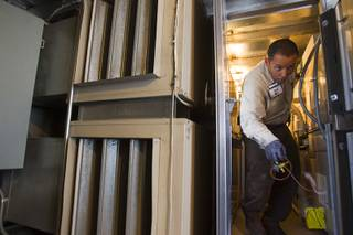 Stephen Molina, an HVAC technician for the Clark County School District, makes his way through a narrow passage between air handling units at Cashman Middle School Tuesday, Sept. 17, 2013. As the effects of the recession continue to affect school operations and deferred maintenance costs continue to rise, the CCSD is finding it difficult to maintain school facilities.