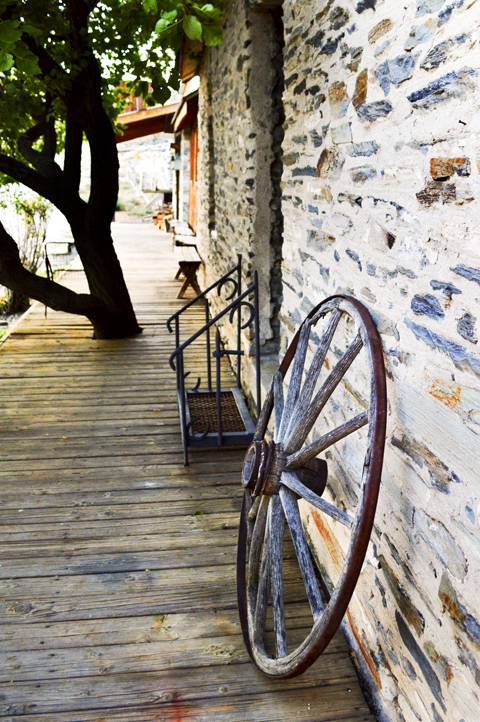 A wagon wheel sits along side of the Belmont Inn and Saloon.