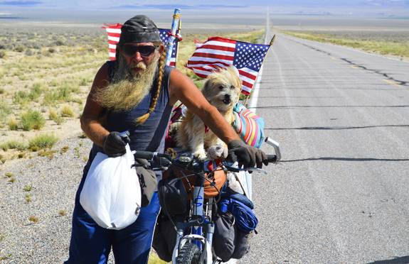 Leo Dever and Sassy Max, a bright-eyed 4-year-old Shih Tzu-terrier mix, on Highway 375 walk up the Queens City Summit outside of Rachel, NV, Tuesday, Sept. 17, 2013.  Leo and Sassy are riding across America on a Cannondale mountain bike.