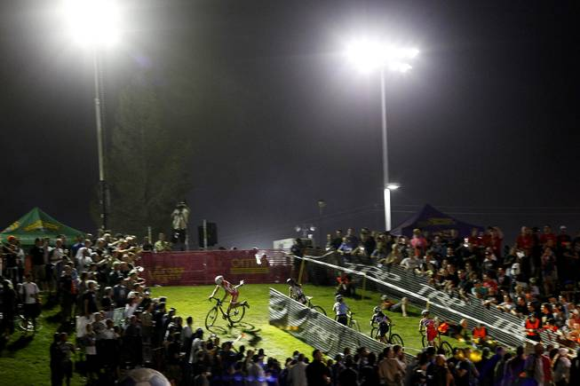 Women leap back on their bikes after negotiating obstacles on a hill during the Cross Vegas cyclocross race Wednesday, Sept. 18, 2013. The women's race was won by Katerina Nash from the Czech Republic.