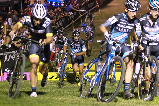 Cyclists in the elite men category charge over barriers and up a hill during the Cross Vegas cyclocross race Wednesday, Sept. 18, 2013. The race was won by two-time and current world champion Sven Nys of Belgium.
