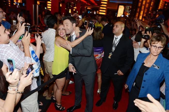 Ben Affleck poses for photos with a fan at the ...