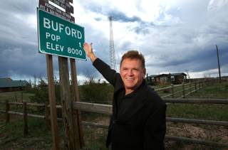 Don Sammons, former owner of the town of Buford, Wyoming, is photographed next to a sign indicating the town's population on September 18, 2013. The town consists of a convenience store, gas station, and modular home on 9.9 acres of land. The town was put up for auction on April 5, 2012, with the highest bid of $900,000 by Vietnamese entrepreneur Pham Dinh Nguyen.