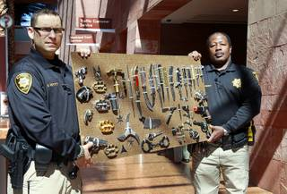 Clark County Deputy Marshals Mike Petty. left, and Ronald Ramsey show off a display of confiscated weapons and prohibited items at the Regional Justice Center Thursday, September 19, 2013.