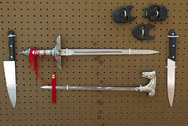 A Nazi replica sword, top, is shown in a display of confiscated weapons and prohibited items at the Regional Justice Center Thursday, September 19, 2013. The lower sword was hidden in a walking cane.