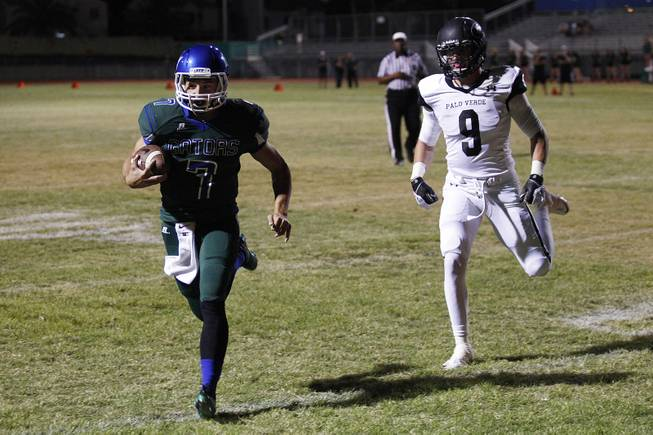 Green Valley quarterback Christian Lopez slips into the end zone past Palo Verde tight end .Jake Ortale during their game Friday, Sept. 20, 2013. Green Valley won the game in overtime 42-41.