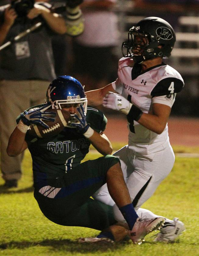 Green Valley wide receiver Gio Hernandez pulls in a touchdown pass while being covered by Palo Verde defensive back Darrion Finn during their game Friday, Sept. 20, 2013. Green Valley won the game in overtime 42-41.