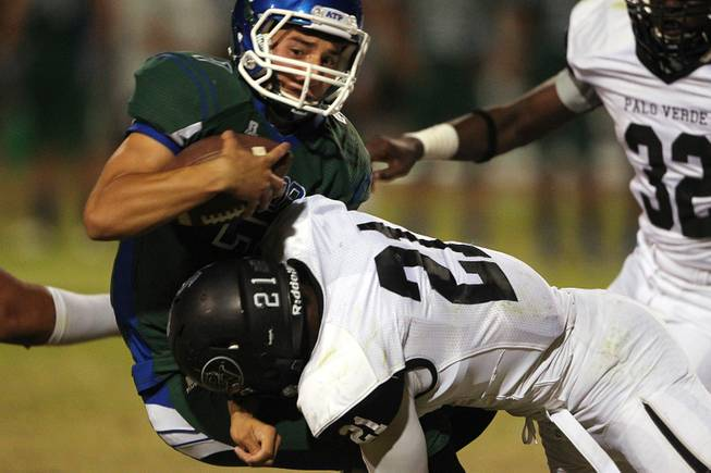 Green Valley quarterback Christian Lopez is dropped for a loss by Palo Verde linebacker Jaren Campbell during their game Friday, Sept. 20, 2013. Green Valley won the game in overtime 42-41.