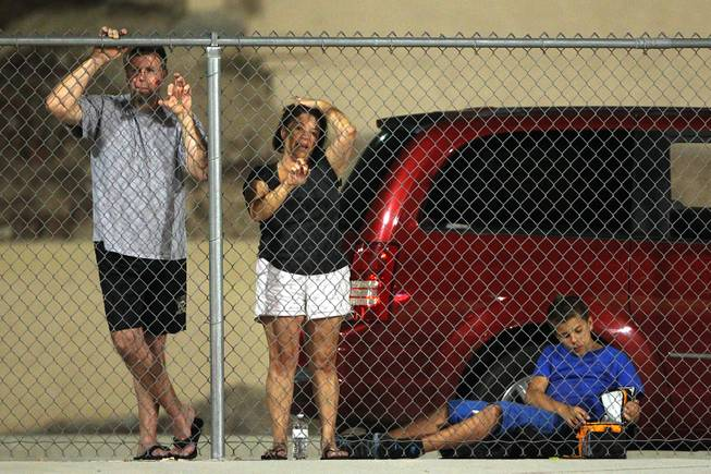 Bystanders watch Green Valley take on Palo Verde from the free section outside the fence Friday, Sept. 20, 2013. Green Valley won the game in overtime 42-41.