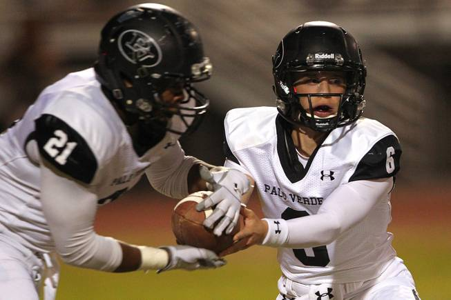 Palo Verde quarterback Parker Rost hands off to running back Jaren Campbell during their game against Green Valley Friday, Sept. 20, 2013. Green Valley won the game in overtime 42-41.