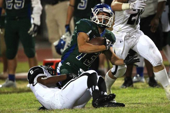 Green Valley wide receiver Kyler Chavez is tackled by Palo Verde defensive back Christopher Johnson during their game Friday, Sept. 20, 2013. Green Valley won the game in overtime 42-41.
