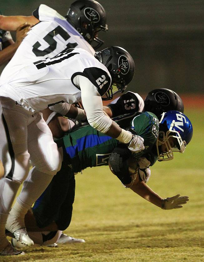 Green Valley running back Albert Lake is taken down by Palo Verde's Griffin Kemp, Jaren Campbell and Jordan Bruner during their game Friday, Sept. 20, 2013. Green Valley won the game in overtime 42-41.