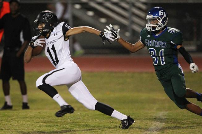 Palo Verde running back Ty Fuller gets past Green Valley defensive back Kyle Parker during their game Friday, Sept. 20, 2013. Green Valley won the game in overtime 42-41.