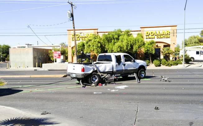 The scene of a two-vehicle crash at Bonanza Road and Lamb Boulevard in which, Metro Police said, a pickup truck careened into a bus stop. Three children at the bus stop were injured, police said. The  white ford truck that hit a bus stop on bonanza, pieces of bus stop can be seen under car, Friday, Sept. 20, 2013.