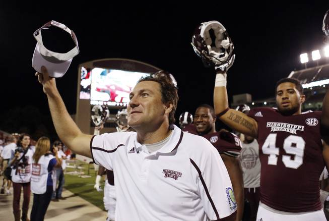 Mississippi State football coach Dan Mullen celebrates his team's 62-7 win over Troy in their NCAA college football game at Davis Wade Stadium in Starkville, Miss., on Saturday, Sept. 21, 2013. (AP Photo/