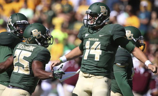 Baylor quarterback Bryce Petty (14) celebrates his touchdown against Louisiana-Monroe  with teammate Lache Seastrunk (25) during the first half of an NCAA college football game, Saturday, Sept. 21, 2013, in Waco, Texas.