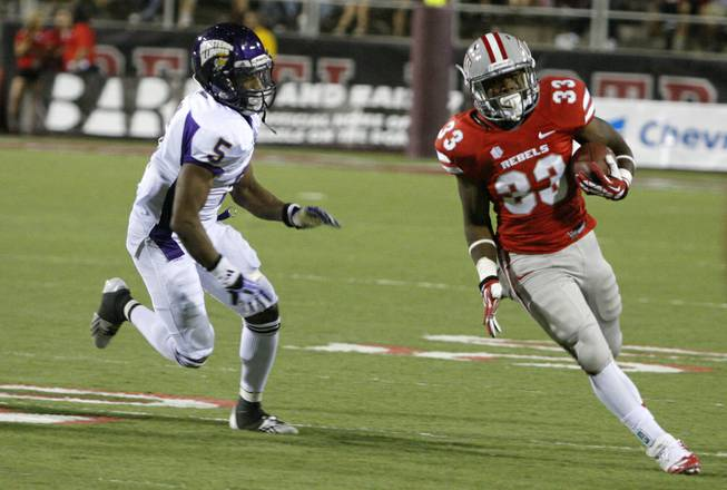 UNLV junior running back Shaquille Murray-Lawrence runs past Western Illinois junior defensive back Martinez Davis in the fourth quarter at Sam Boyd Stadium Saturday, Sept. 21, 2013.