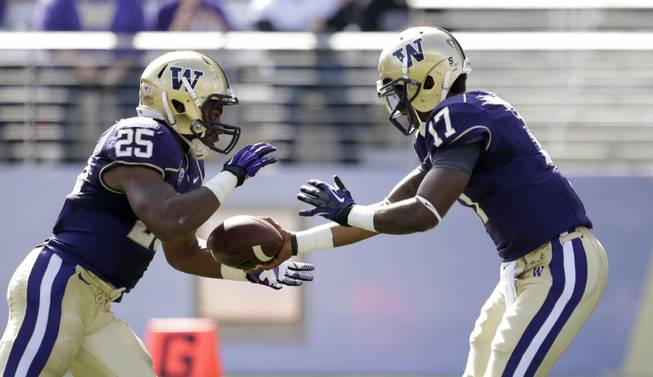 Washington's Keith Price (17) hands off to Bishop Sankey against Idaho State in the first half of an NCAA college football game Saturday, Sept. 21, 2013, in Seattle.