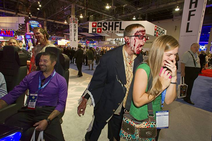"A zombie goes after Marie Kay Williams by a display of Aristocrat's ""Walking Dead"" video slot machines during the G2E convention at the Sands Expo Center Tuesday, Sept. 24, 2013. The slots are themed after AMC's Walking Dead television drama."