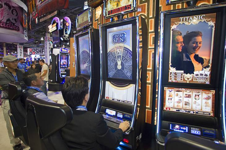 "People try out new Titanic slot machines by Bally Technologies during the G2E convention at the Sands Expo Center Tuesday, Sept. 24, 2013.  The slots are themed after the 1997 ""Titanic"" movie starring Leonardo DiCaprio and Kate Winslet."