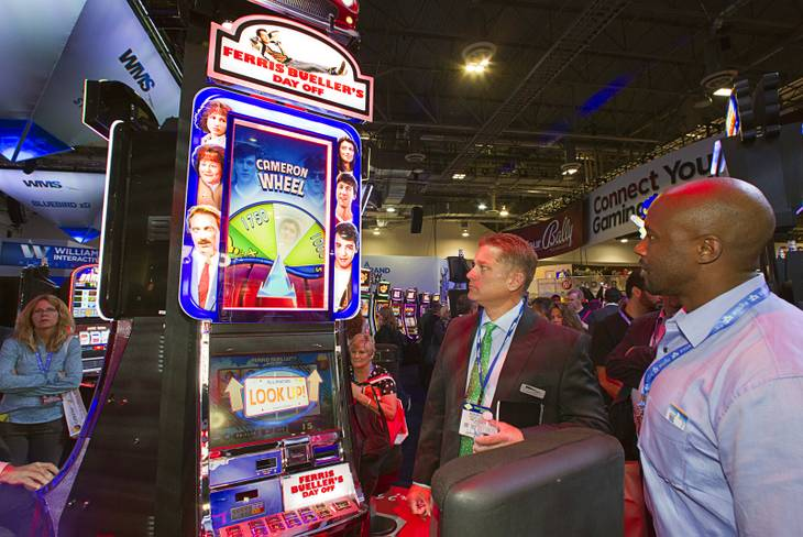 "People look over a ""Ferris Bueller's Day Off "" video slot machines by WMS Gaming during the G2E convention at the Sands Expo Center Tuesday, Sept. 24, 2013. The slots are themed on the 1986 movie starring Matthew Broderick."