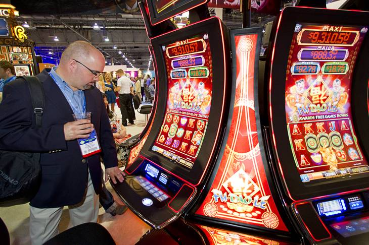 Jose Figueroa of Puerto Rico looks over slot machines in Bally Technologies' Pro Wave cabinets during the G2E convention at the Sands Expo Center Tuesday, Sept. 24, 2013.