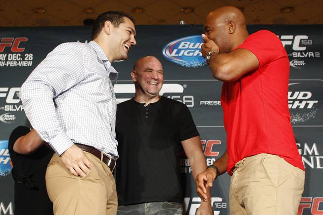 Chris Weidman and Anderson Silva laugh as they face off during a news conference to promote their December fight at UFC 168 Tuesday, Sept. 24, 2013. Silva was covering his mouth in reference to the kiss he gave Weidman during the weigh in for their previous fight.