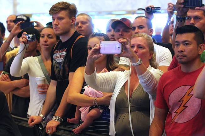 Fans watch a news conference to promote UFC 168 Tuesday, Sept. 24, 2013.