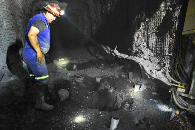 Paul Sierra, a Newmont Mining Corp. driller, looks down a hole in the Leeville mine west of Elko on Sept. 26, 2013. He's about 2,000 feet underground, preparing holes that will be filled with explosives.