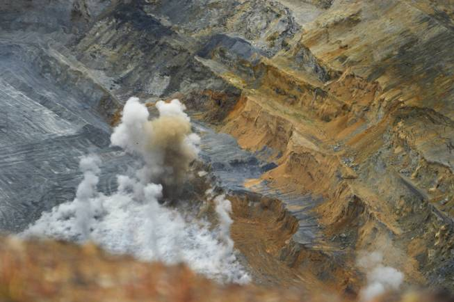 A blast goes off near the bottom of an open pit at the Goldmont Mining Corp.'s Carlin complex wet of Elko on Sept. 26, 2013.