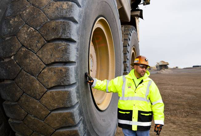 Benjie Gallegos of Newmont Mining Corp. stands next to a Caterpillar dump truck with tires that are more than 13 feet tall. The photo was taken at the Carlin mine complex west of Elko on Sept. 26, 2013.