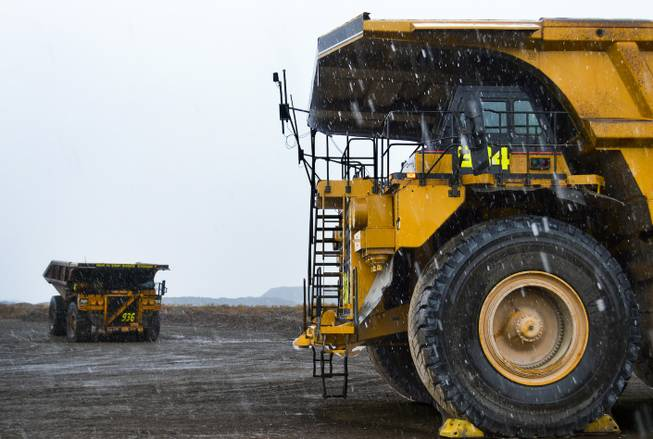 Two massive Caterpillar dump trucks with tires that are more than 13 feet tall stand in the snow at the Carlin mine complex west of Elko on Sept. 26, 2013.