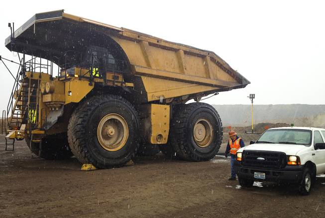 A Caterpillar dump truck dwarfs the man and work truck next to it on Sept. 26, 2013, at Newmont Mining Corp.'s Carlin complex west of Elko.