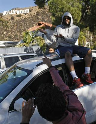 Andre Anderson, visiting from Philadelphia, is photographed Sept. 27, 2013, on Deronda Drive in the Beachwood Canyon area of Los Angeles. Residents in the Beachwood Canyon area are fighting with the Hollywoodland Homeowners Association over tourists looking at the Hollywood sign.