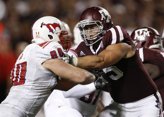 SMU defensive end Zach Wood (90) and Texas A&M offensive linesman Jake Matthews (75) lock up on the line in the fourth quarter during an NCAA college football game Saturday, Sept. 21, 2013, in College Station, Texas. Texas A&M won 42-13.