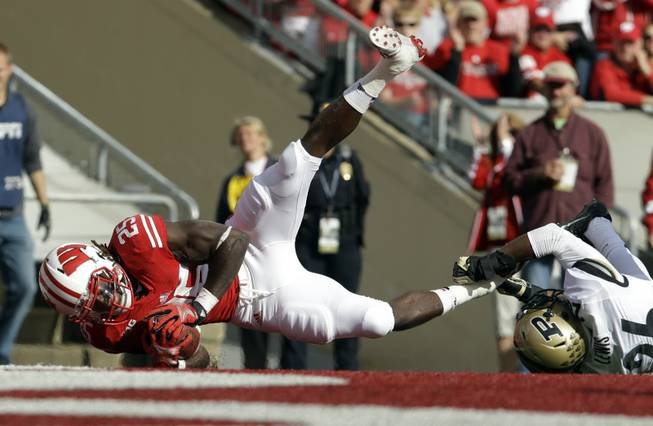 Wisconsin's Melvin Gordon (25) breaks away from Purdue's Antoine Lewis for a touchdown run during the first half of an NCAA college football game Saturday, Sept. 21, 2013, in Madison, Wis.