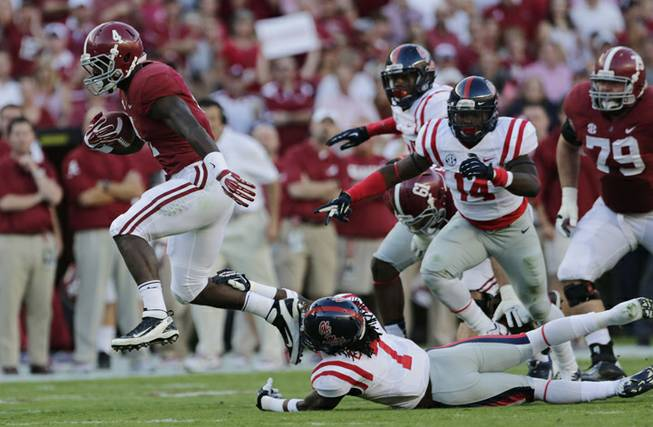 Alabama running back T.J. Yeldon (4) runs for yardage as Mississippi defensive back Trae Elston (7) defends during the first half of an NCAA college football game against Mississippi in Tuscaloosa, Ala., Saturday, Sept. 28, 2013.