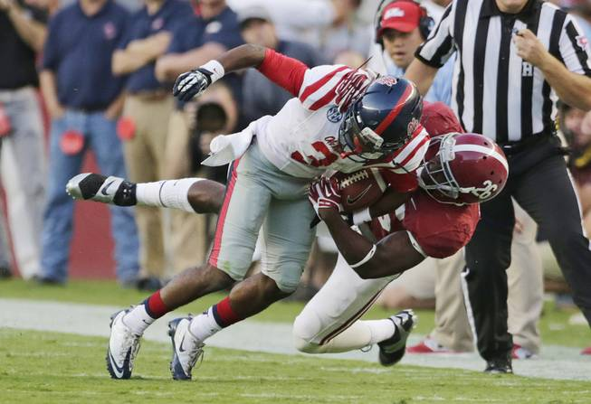 Mississippi running back Jeff Scott (3) is taken down by Alabama defensive back Landon Collins (26) during the first half of an NCAA college football game in Tuscaloosa, Ala., Saturday, Sept. 28, 2013.