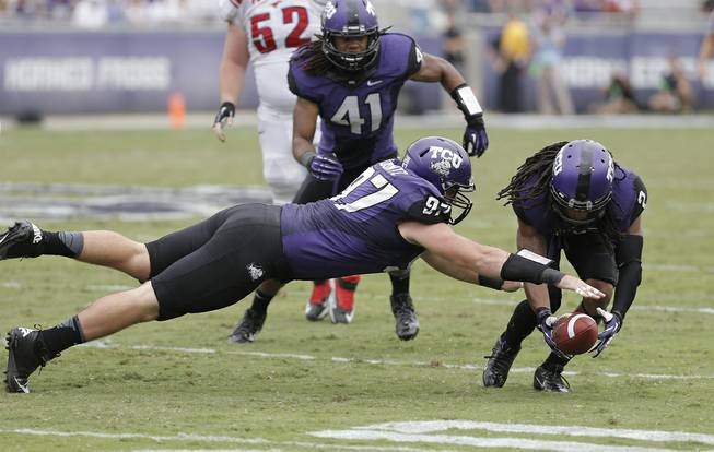 TCU defensive end Jon Koontz (97), cornerback Jason Verrett (2) and linebacker Jonathan Anderson (41) recover a SMU fumble during the first half of an NCAA college football game Saturday, Sept. 28, 2013, in Fort Worth, Texas. TCU won 48-17.