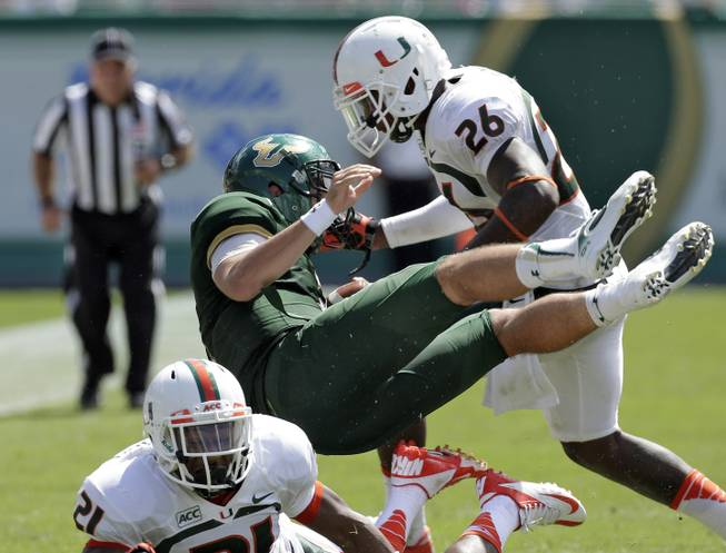 Miami defensive back Antonio Crawford (21) and defensive back Rayshawn Jenkins (26) team up to send South Florida quarterback Steven Bench flying on a third quarter tackle during an NCAA college football game Saturday, Sept. 28, 2013, in Tampa, Fla. Miami won the game 49-21.