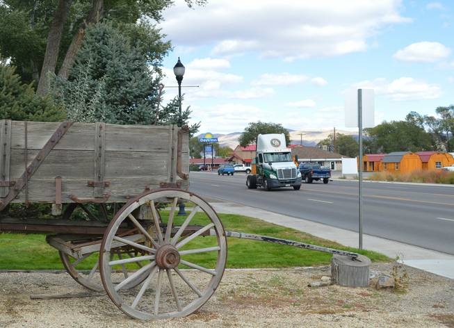 A tractor trailer rig goes by an old wagon at Sherman Station, which dates to the 1880s, in Elko on Sept. 27, 2013.