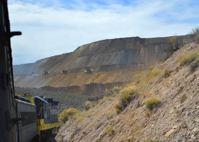 A Nevada Northern Railway train goes around a bend by a copper mine outside of Ely on Sept. 30, 2013. The rail line was put in originally to handle loads of copper, but it no longer does.