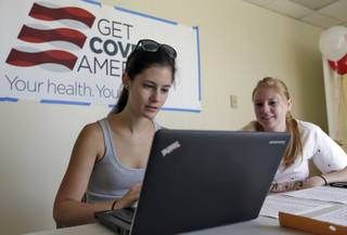Ashley Hentze, left, of Lakeland, Fla., gets help signing up for the Affordable Care Act from Kristen Nash, a volunteer with Enroll America, a private, non-profit organization running a grassroots campaign to encourage people to sign up for health care, Tuesday, Oct. 1, 2013  After months of build-up, Florida residents can start shopping for health insurance on government-run online marketplaces as the key component of the Affordable Care Act goes live.