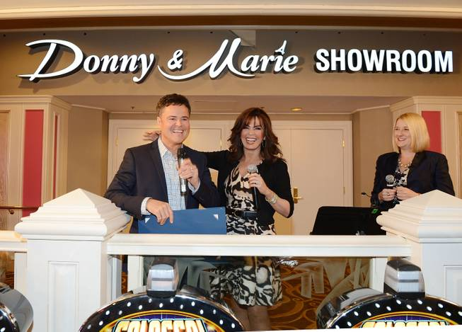Flamingo Las Vegas Regional President Eileen Moore, right, Donny Osmond and Marie Osmond unveil the signage for the newly renamed Donny & Marie Showroom at Flamingo Las Vegas on Wednesday, Oct.  2, 2013.