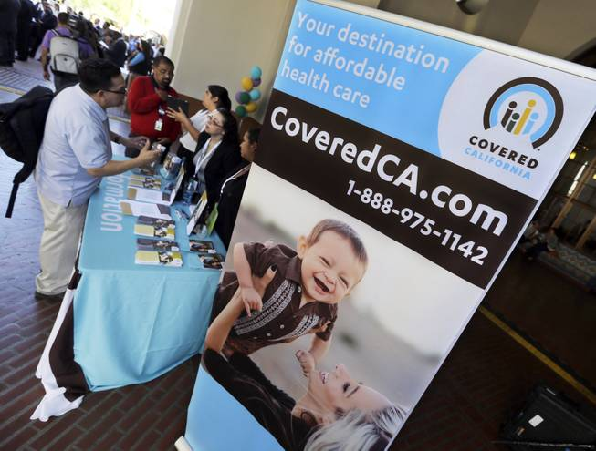 An information table is busy at Union Station in downtown Los Angeles as people seek information on state-provided health insurance, while a celebration is underway to inaugurate the first day people can enroll, Tuesday, Oct. 1, 2013.