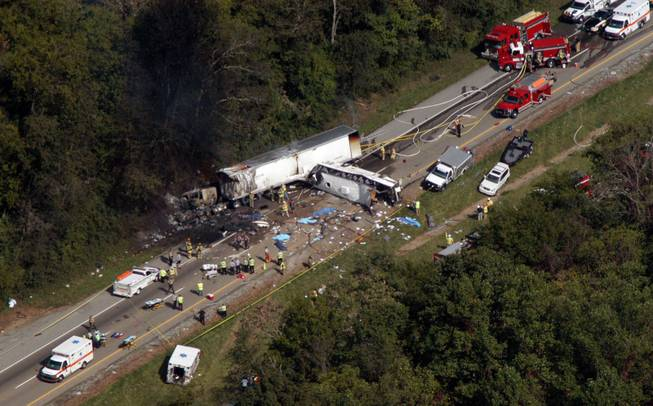 In this aerial photo, emergency workers respond to a crash involving a church bus and a tractor-trailer near Dandridge, Tenn., on Wednesday, Oct. 2, 2013.  Authorities say a tire on the bus blew out and the bus hit the tractor-trailer and a sport utility vehicle, killing eight people.