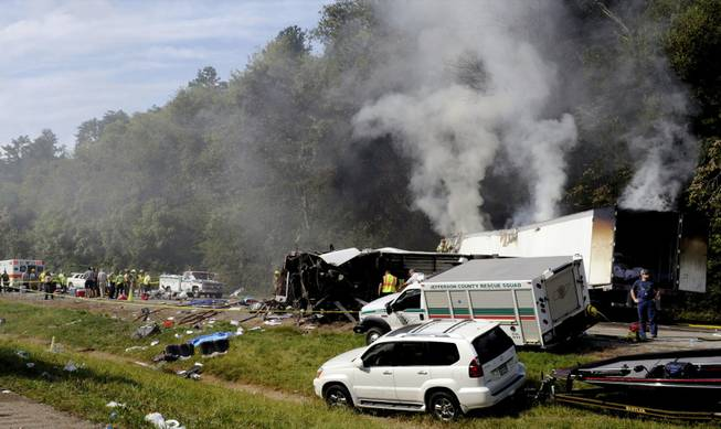 Emergency personnel search the scene near a collision involving a bus on I-40, in Dandridge, Tenn, on Wednesday, Oct. 2, 2013. A spokeswoman for Tennessee's Safety Department says there are multiple fatalities and injuries in an interstate bus crash between a passenger bus, a tractor-trailer and another vehicle.