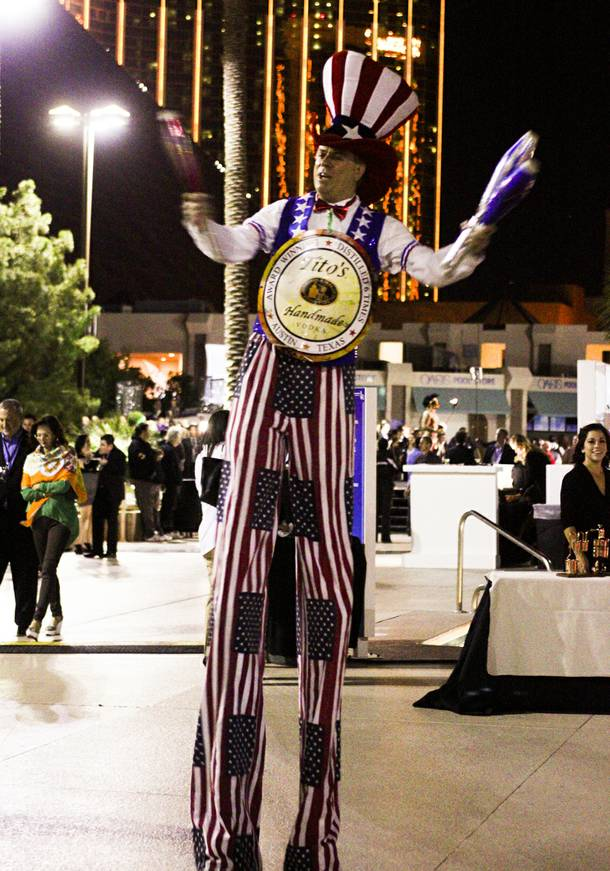 A juggling man on stilts wearing a Tito's Handmade Vodka sign entertains guests during the Epicurean Charitable Foundations M.E.N.U.S. (Mentoring & Educating Nevadas Upcoming Students) fundraising event at the Luxor Oasis Pool on Friday, Oct. 4, 2013.