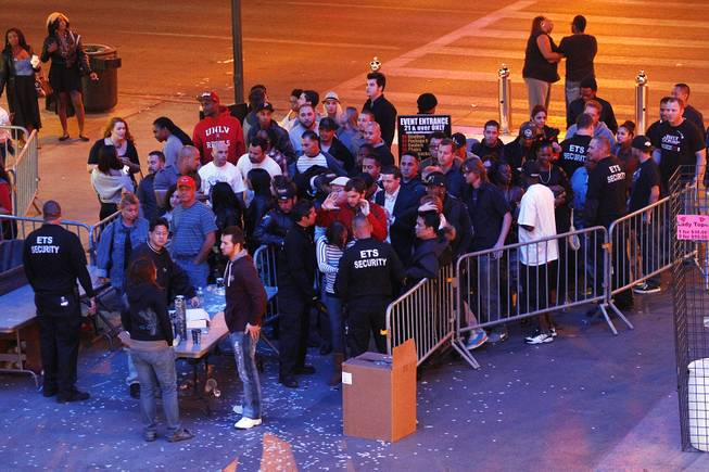 People get backed up while they are searched and have their identification checked before entering the Fremont Street Experience early Saturday, Oct. 5, 2013.